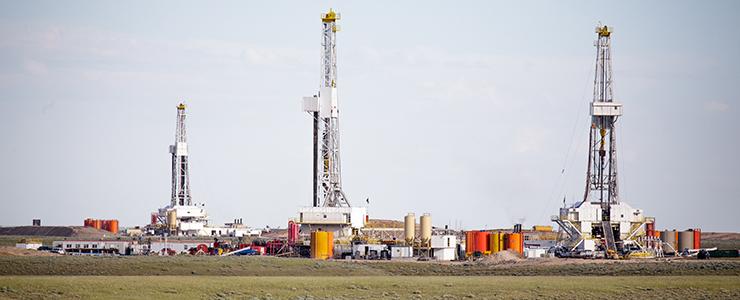 hydro- fracking derricks drilling natural gas on a plain