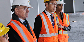 Four people line up in hard hats