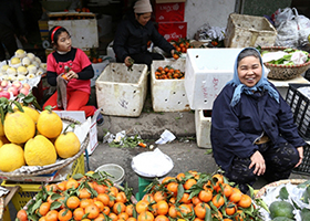 Image of woman sitting amongst produce in open-air market