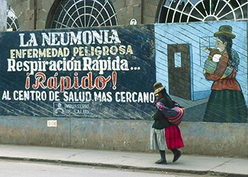 Woman walking by public health billboard about pneumonia