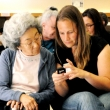 At the North Berkeley Senior Center, public health graduate students show seniors how to operate a cell phone.