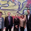 Image of five people standing in front of a large piece of artwork.