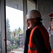 Image of three people in hard hats look out of a window in a construction area.