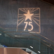 75th Anniversary logo projected onto an interior wall