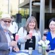 Three people raise wine glasses in celebration