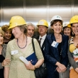 Group of people, some in hard hats, pack into an elevator