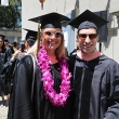 Man and woman in cap and gown smile