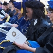 Row of people in cap and gowns reading pamphlets.