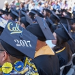 A row of people sitting in cap and gowns.