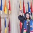 Woman in cap and gown raises arm in the air.