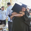 Two people in cap and gown embrace.