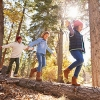 three children walk across a log